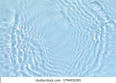 Blurred transparent blue colored clear calm water surface texture with splashes and bubbles. Trendy abstract nature background. Water waves in sunlight.