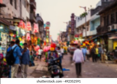 Blurred travel backgrounds - Grand market in the evening in Delhi, India. Typical shops and cafes, selling souvenirs