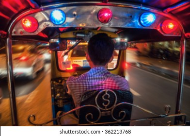 Blurred travel backgrounds - Riding Tuk Tuk at night in Bangkok, Thailand - popular among tourists city taxi
