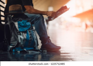 Blurred - traveler with backpack and hat, during train ride on a wooden bench at the train station, Concept to plan summer travel and check route with map.