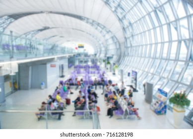 Blurred Traveling concept. Travelers asian walking with a luggage at airport terminal and airport terminal blurred crowd of travel people on the background.
