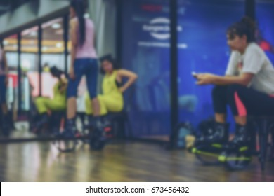 Blurred of an unidentified group of woman  doing exercises fitness with kangoo shoes in glass fitness studio.The best background for use.Cross processing and Split tone new colour trend like process.