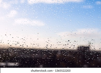 Blurred urban background with blue cloudy sky behind wet window. Water drops on glass in a rainy day. Conceptual mood of hope image.