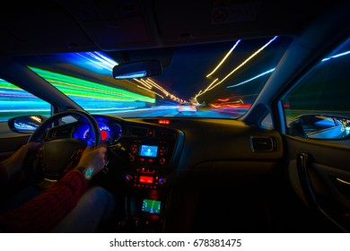 blurred urban look of the car movement nights longexposure, Hands on the wheel, driving at high speed, navigating the path. Blurred road lights