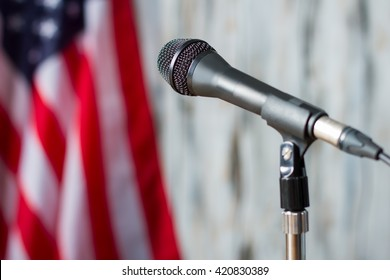 Blurred US flag and microphone. Microphone on stand beside banner. Entire nation will be watching. Tribune waiting for the speaker.