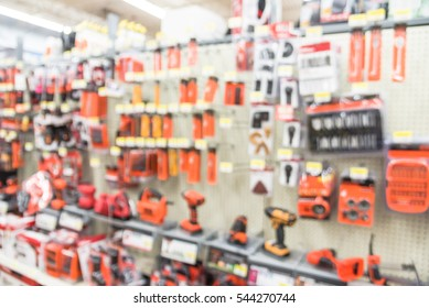 Blurred variety of power tools at tools department in local store Humble, Texas, US. Row of cordless drills, driver, jigsaw, circular saw kit and drill bits. Depicting carpentry and construction tools
