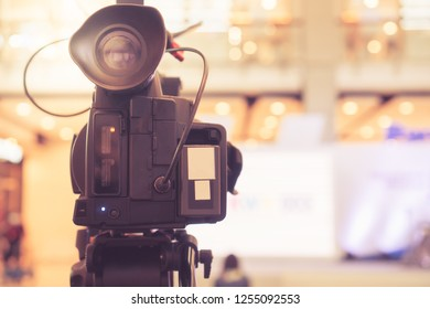 Blurred of Video camera recording film shooting of grand opening in conference hall Live streaming wifi microphone sending for presentation with bokeh light background. Media Production Process Concept