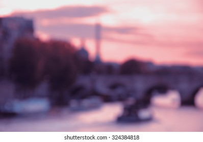 Blurred view of bridge over the Seine river and Eiffel tower at background at sunset. Bokeh. Toned photo.