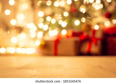Blurred view of christmas tree in bright warm lights and beautiful presents under it, focus on the floor. Festive atmosphere, new year holidays background. - Shutterstock ID 1851545476