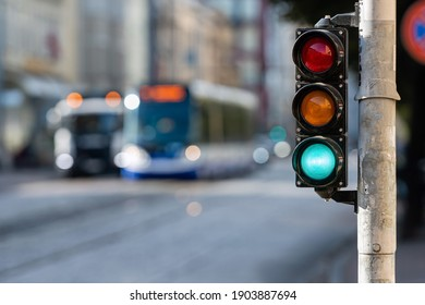 blurred view of city traffic with traffic lights, in the foreground a traffic light with a green light