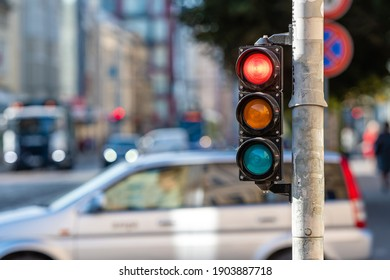 blurred view of city traffic with traffic lights, in the foreground a traffic light with a red light