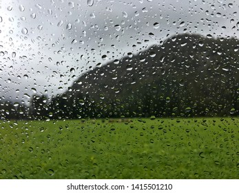 Blurred view of cows on green field, big mountain in rainy day with rain drops splashing windscreen