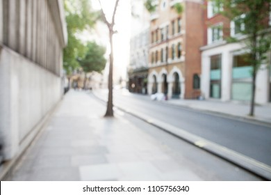 Blurred view of London street with shops, trees and buildings. Can be used as background