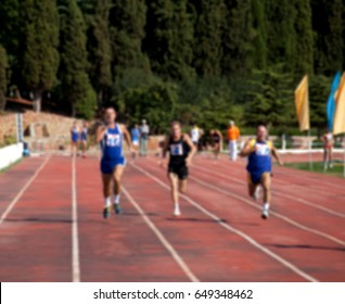 Blurred view of man athletic running competition at stadium not in focus. Use as background.