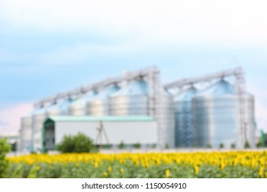 Blurred view of modern granaries for storing cereal grains in field
