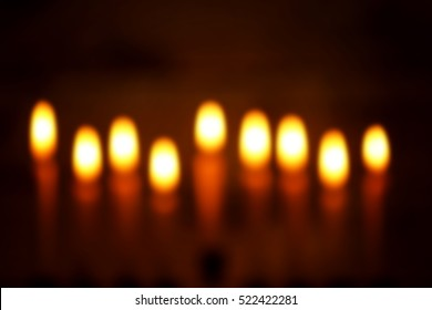 Blurred view of nine burning candles on dark background. Hanukkah concept