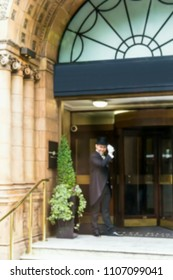 Blurred view of the receptionist porter in a tuxedo raises his hat to meet guests near main entrance of one of famous hotel in London, UK