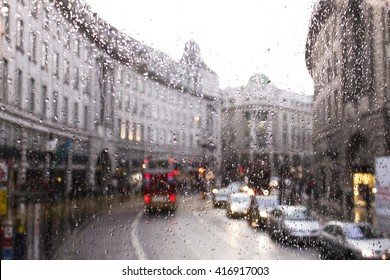 blurred view of road traffic in London on a rainy day through the bus window. raindrops on the glass window of the bus.