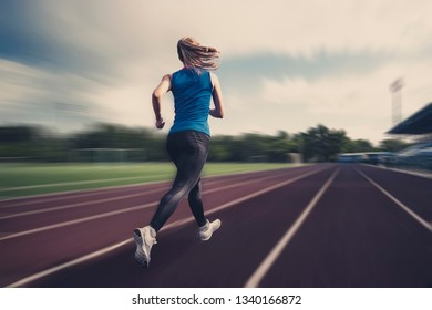 Blurred view of running girl on stadium at competition. Use as background. Athletics at the stadium