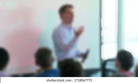 Blurred view Senior business mentor coaching executive managers team at corporate group meeting in conference room, company ceo giving presentation to partners discussing new strategic plan