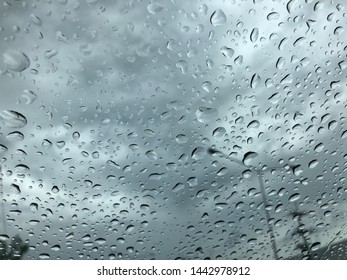 blurred view of sky through the windshield on a rainny day. rain drop on windshield. blurred blackground.rain drop blackground