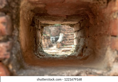 Blurred view through focused loophole in brick wall with ancient masonry on Wat Mahatha temple in Ayutthaya, Thailand. Light at the end of tunnel.