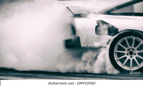 Blurred vintage image of car drifting with a lot of smoke on race track. Motor sport concept.