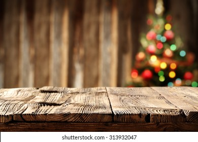 blurred wall background with xmas tree of few colors lights and shabby table