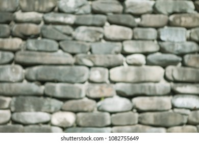 blurred wall is made of natural rounded sandstone stone of gray color. Concept Black Sea masonry.