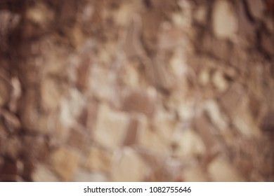 blurred wall is made of natural sandstone from a gray color. The concept of the Black Sea masonry.