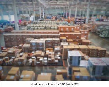 Blurred warehouse interior environment with full of catton boxes and pallets stacking in storage area in each location for inventory management and distribution