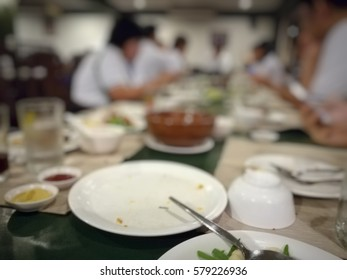 Blurred waste food and people on round table after lunch