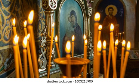 Blurred wax burning candles in an orthodox church on the icon background.