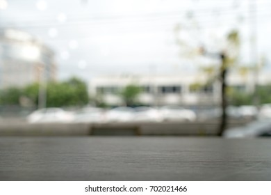Blurred white cars on the traffic with dark brown wooden table in the cafe for montage product display