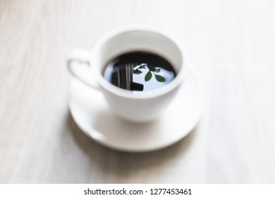 Blurred, white coffee mug Reflection, leaves and sky in a cup black coffee