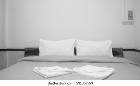 Blurred of white pillow and bedding sheets on natural white wall bedroom background, Messy bed concept.