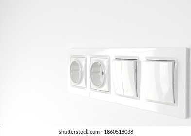 Blurred. White plastic walk-through switches and sockets on a white wall