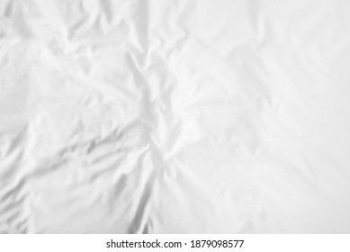 Blurred white wrinkled bedsheet or fabic texture rippled surface background. Unmade of bedsheet in the morning. Top view and soft focus with copy space background.