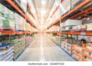 Blurred wholesale store aisle with big boxes of product from floor to ceiling racks. Large warehouse wholesale in America. Defocused industrial distribution storehouse abstract background