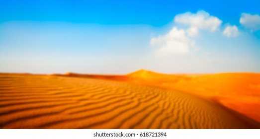 Blurred wide banner panorama of sand and white clouds on a blue sky