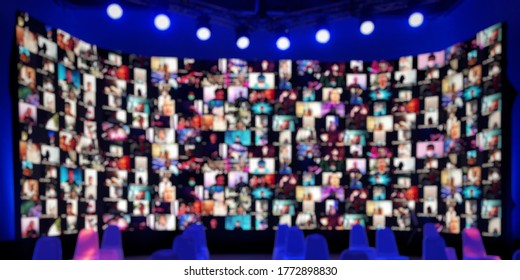 Blurred wide LED screen of many people faces join big online  event or live conference.Video online conference.Social distancing 				 reduce risk coronavirus.New normal event production.Online seminar.