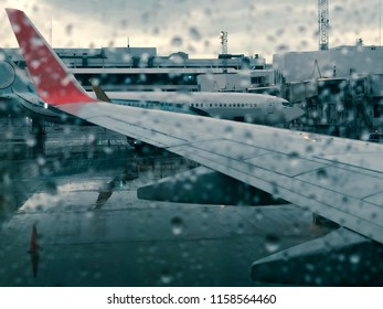 Blurred of wing of airplane see through the rain drop on window of plane that land on the airport in the rainy evening with the cloudy light.The runway wet with water. Vintage style and blue sepia