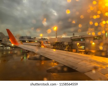 Blurred of wing of airplane see through the rain drop on window of plane that land on the airport in the rainy evening with the twilight light.The runway wet with water and the building open the light