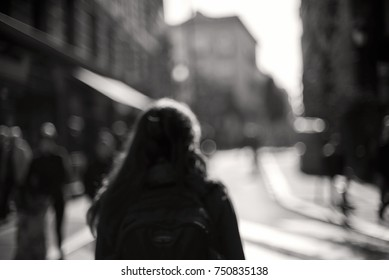 Blurred woman from behind walking through blurred city. De-focused, black and white image with some people commuting and a woman in the middle. Sad or loneliness feelings, maybe fear concept too.