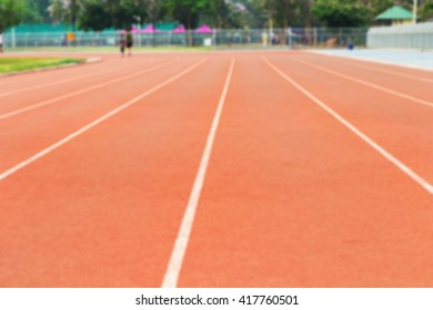 Blurred woman and child jogging on track in evening