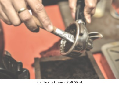 Blurred of woman making espresso with clearing old hot coffee grain out from portafilter.Close up of professional barista concept.