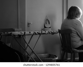 A Blurred Woman Sitting Towards a Light Source with Her Back Towards an Ironing Board, Showing a Depiction of Rejection and Depression within a Scruffy Interior and Appliances.