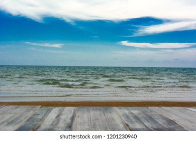Blurred wood floor with beach and sea over blue sky and clouds. Montage of see for product content. Copy space for text or products.