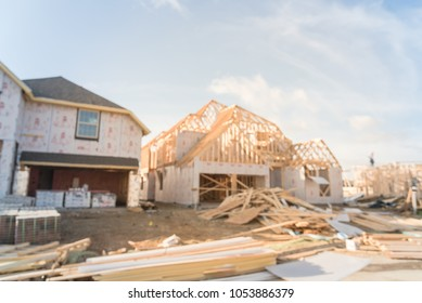 Blurred wood frame house under construction beam pile logs in suburban Irving, Texas, USA. Abstract workers and builders working on new stick built house near envelope sealing sheathing homes
