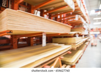 Blurred wooden bars from floor to ceiling at lumber yard of hardware store in America. Rack of pre-cut panel, mill wood timber, red oak, poplar, cedar, whitewood board, siding, plywood on flatbed cart